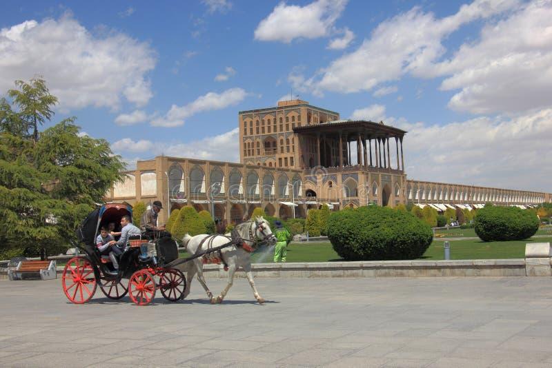 En hästvagn med folk på den Naqsh-e Jahan fyrkanten eller Iman Square med den berömda Ali Qapu Palace i bakgrunden , i Isfahan, I royaltyfri foto