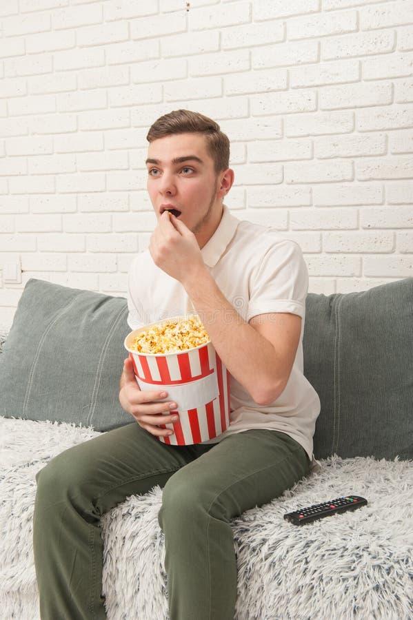 En hållande ögonen på TV för tonårs- pojke och ätapopcorn arkivbild