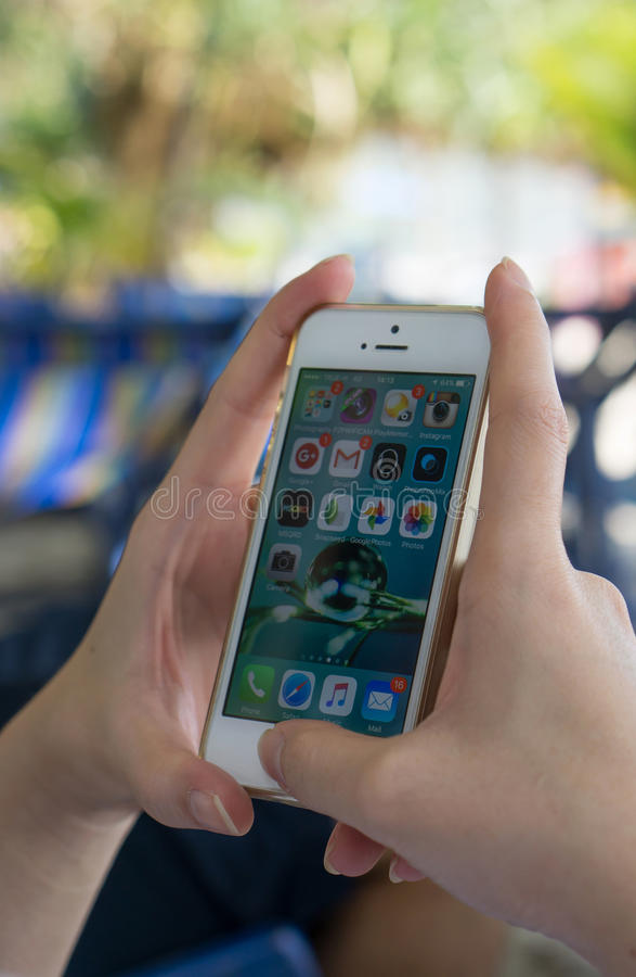 En hållande iphone för kvinnahand med startskärmensidan royaltyfri fotografi