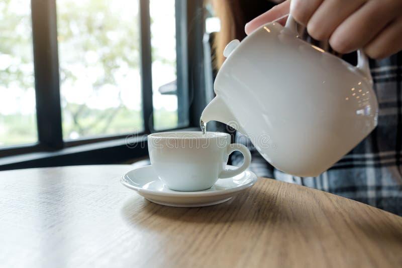 En hållande tekanna för hand och ett hällande te in i en vit kopp royaltyfri bild