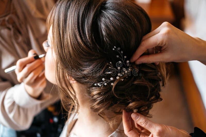 En hårstylist och en sminkkonstnär förbereder en brud för bröllopdagen arkivbild