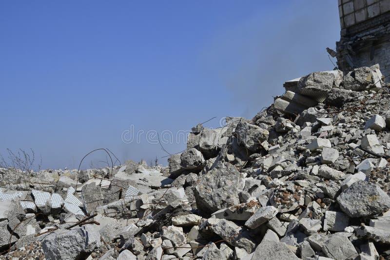 En hög av betongstenar med en del av den förstörda byggnaden mot en klar blå himmel Bakgrund arkivbild