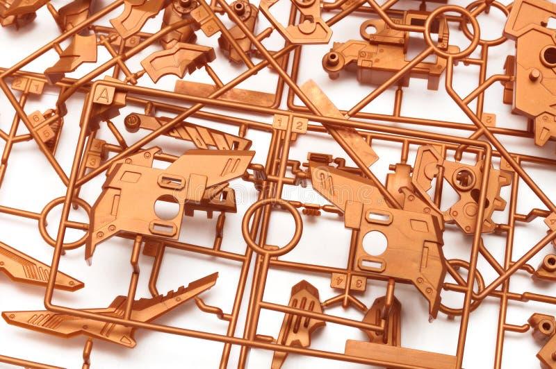 En hög av den metalliska orange plast- uppsättningen för sats för skalamodell med futuristiska robotic delar royaltyfria bilder