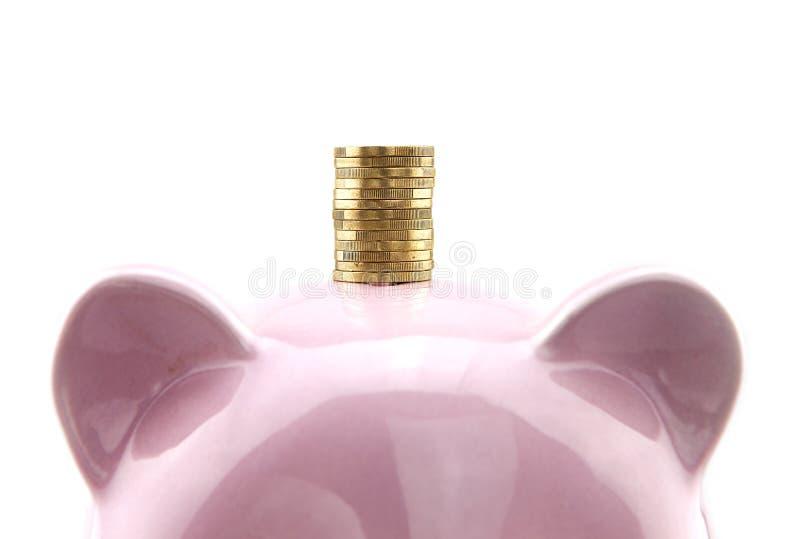 En hög av euromynt på överkanten av spargrisen royaltyfria bilder