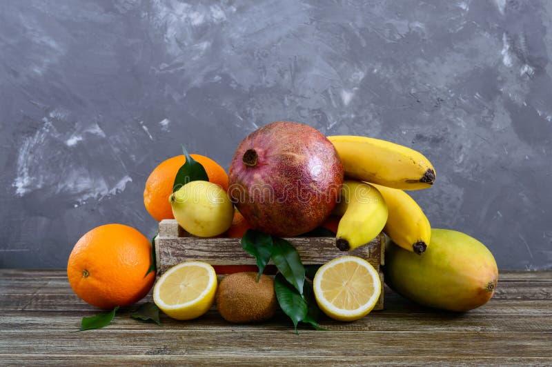 En hög av exotiska fruktbananer, apelsiner, kiwi, granatäpple, mango, guava, citron i en träask royaltyfri bild