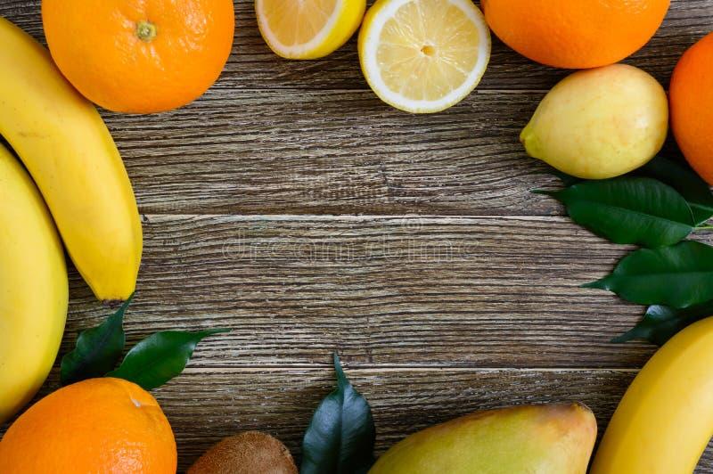 En hög av exotiska fruktbananer, apelsiner, kiwi, mango, guava, citron på en trätabell fritt avstånd arkivfoton