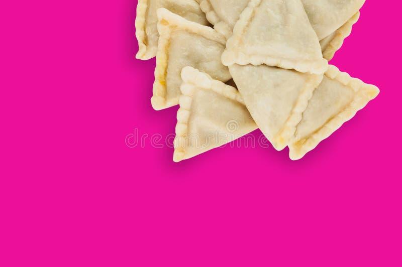 En hög av förberedd vareniki med potatisen eller keso eller kött eller kål på rosa bakgrund royaltyfria bilder