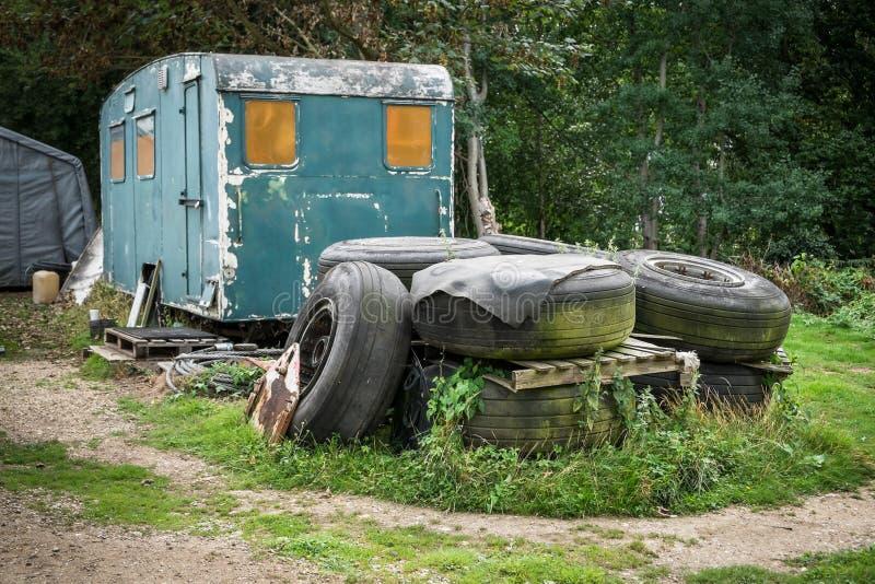 En hög av gamla däck framme av en övergiven husvagn royaltyfri foto