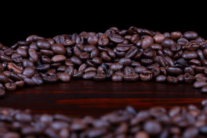 En hög av grillade kaffebönor travde i en cirkel på isolerat mahognyträ arkivfoton