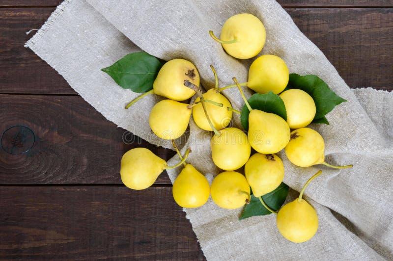En hög av gula päron spridde på en mörk trätabell arkivfoto