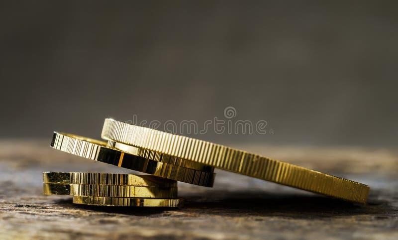 En hög av guld- mynt av olika format på en neutral suddig bakgrund royaltyfria foton