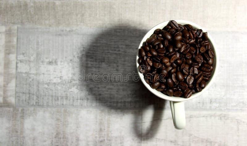 En hög av kaffebönor i en kopp royaltyfria bilder
