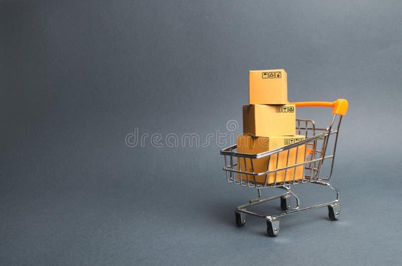 En hög av kartonger i en supermarketspårvagn begrepp av shopping i online-lagret E-kommers, försäljningar och försäljning av gods fotografering för bildbyråer