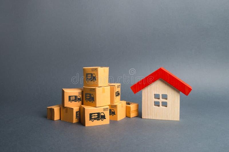 En hög av kartonger och ett trähus Begrepp av att flytta sig till en annan hus eller stad Egenskapstrans. fraktar royaltyfri bild