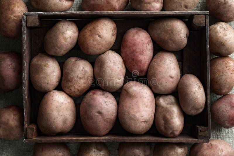 En hög av nya potatisar i en mörk träask Bakgrund för linnekanfas arkivfoto