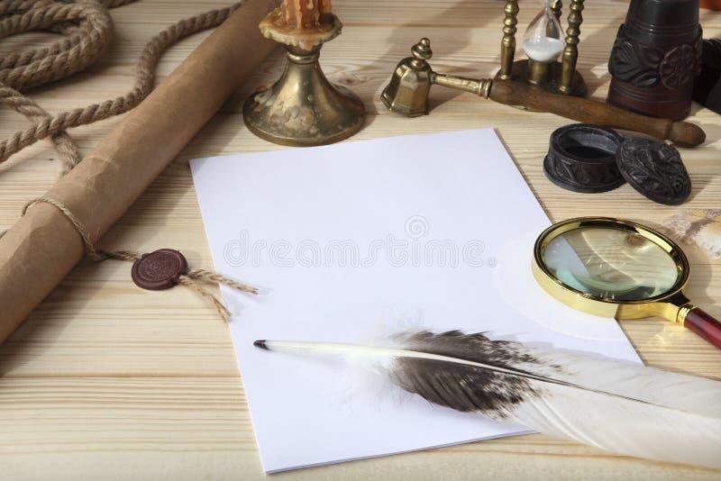 En hög av rengöringpapper, en retro bläckhorn med svart färgpulver, en gåsfjäder, förstoringsglas, en snirkel med en skyddsremsa, royaltyfri foto