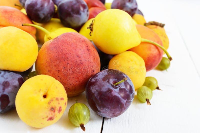 En hög av saftig sommar bär frukt på vita träbakgrundsplommoner, aprikors, päron Skörd från trädgården arkivfoton