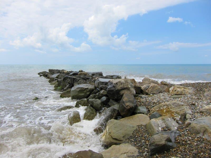 En hög av stenar sträcker ut in i havet royaltyfria foton