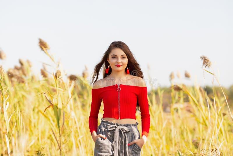 En hög flicka för härlig kvinnlig caucasian högstadium i röd skördöverkanttröja royaltyfri bild