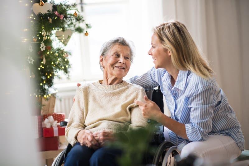 En hög kvinna i rullstol med en vård- besökare hemma på jultid royaltyfria foton