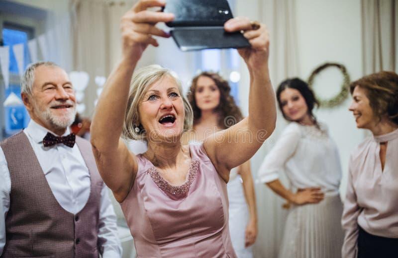 En hög kvinna med maken på bröllop eller födelsedagpartiet som tar selfie med smartphonen arkivfoton