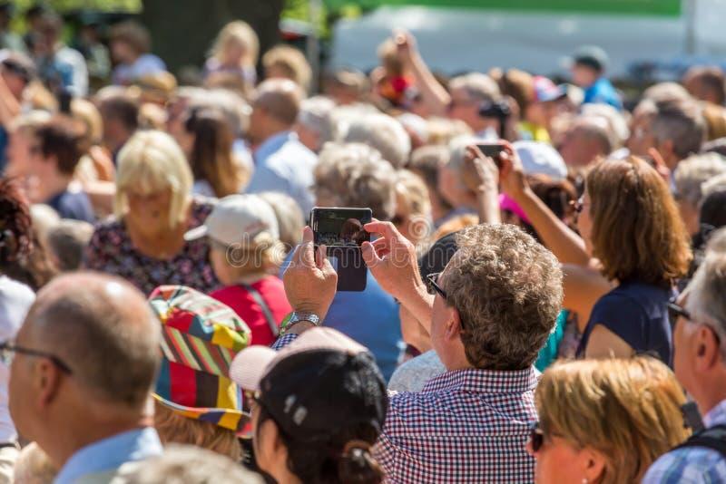 En hög kvinna som rymmer en mobiltelefon som tar bilder royaltyfri foto