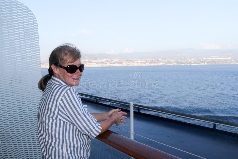 En hög kvinna tycker om sikten från ett skepp som kryssar omkring till och med kanalerna av Messina, Italien arkivbild