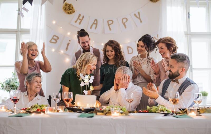 En hög man med den multigeneration familjen som firar födelsedag på det inomhus partiet arkivfoto