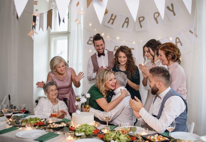 En hög man med den multigeneration familjen som firar födelsedag på det inomhus partiet arkivfoton