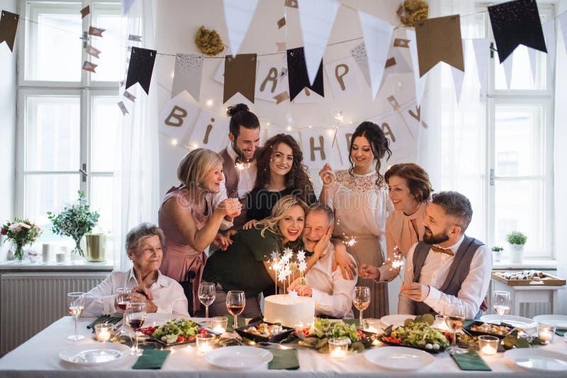 En hög man med den multigeneration familjen som firar födelsedag på det inomhus partiet royaltyfria foton