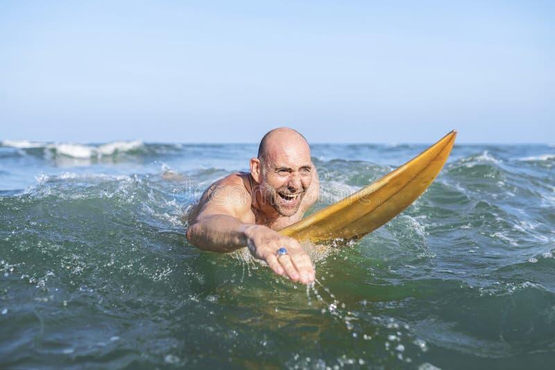 En hög man på en surfingbräda fotografering för bildbyråer