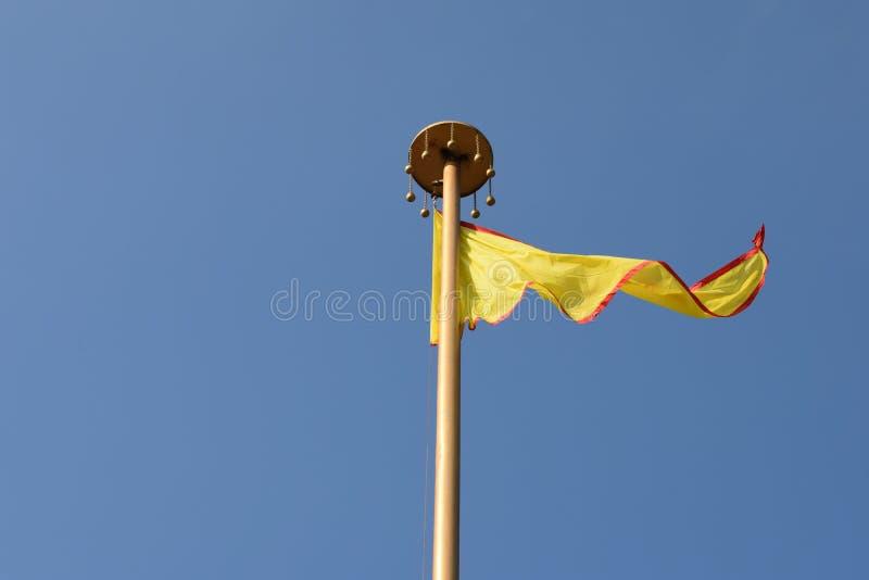 En hög vinkande gul färgad flagga royaltyfri foto