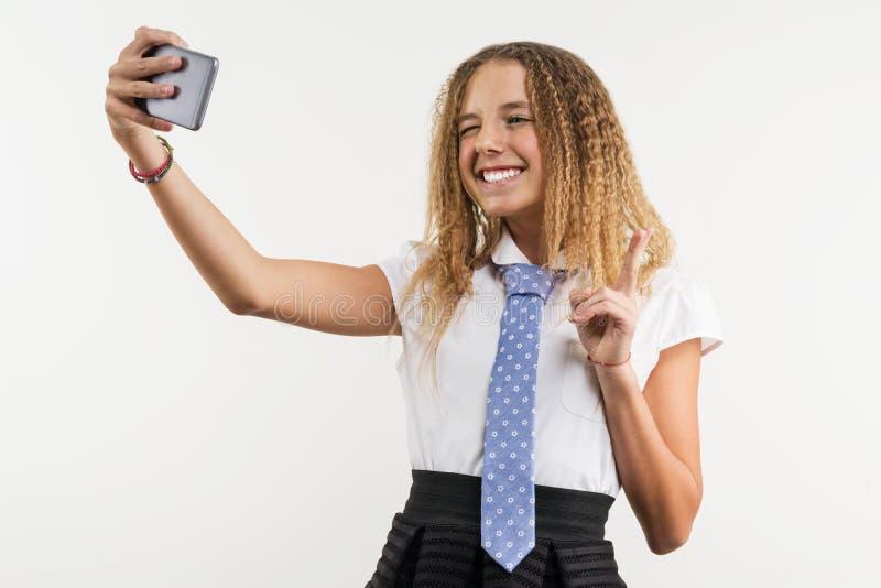 En högstadiumflicka gör selfie genom att använda en smartphone royaltyfri foto
