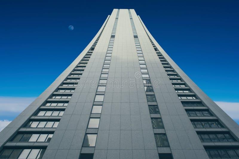 En högväxt byggnad som går in i solnedgånghimmel och regniga moln himlen royaltyfria bilder