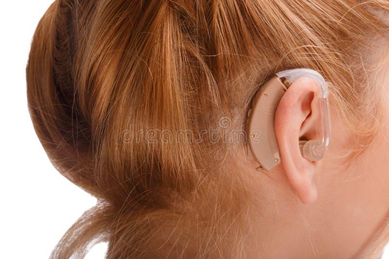 En hörapparat på örat av en flicka med rött hår isolerat royaltyfria foton