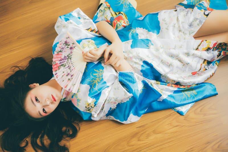 En h?rlig asiatisk flicka och en japansk kimono royaltyfri foto