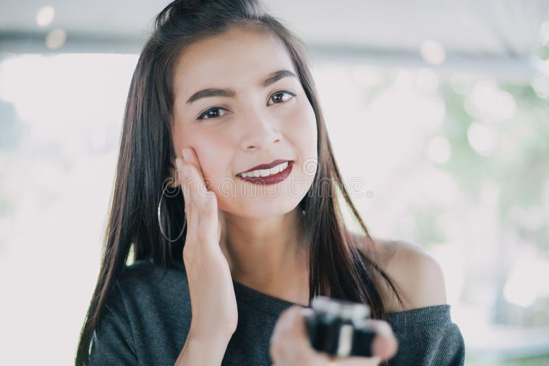 En h?rlig kvinnaasiat som anv?nder en produkt, en fuktighetsbevarande hudkr?m eller en lotion f?r hudomsorg som tar omsorg av hen arkivfoto