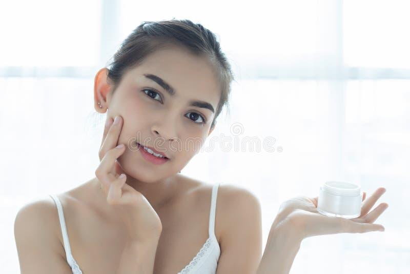 En h?rlig kvinnaasiat som anv?nder en produkt, en fuktighetsbevarande hudkr?m eller en lotion f?r hudomsorg som tar omsorg av hen fotografering för bildbyråer