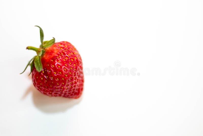 En h?rlig r?d jordgubbe med en gr?n svans ligger p? en vit bakgrund royaltyfri fotografi