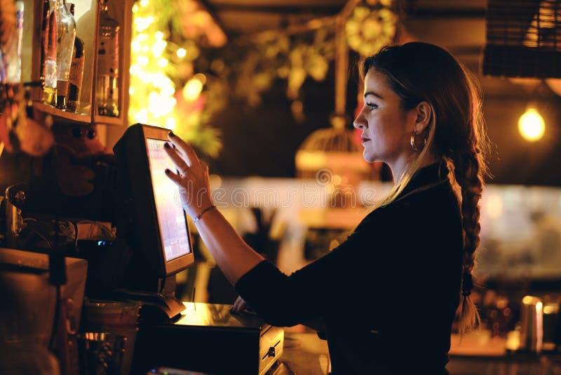 En h?rlig ung kvinna p? skrivbordet i en restaurang arkivfoton