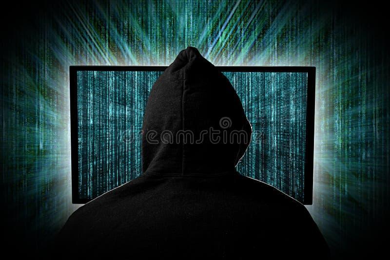En hacker bak glödande datorbildskärmskärm framme av den gröna datoren för hacka för cyber för internet för bakgrund för arkivfoto