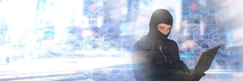 En hacker i balaclava på bärbara datorn med geometriska övergångar royaltyfri foto