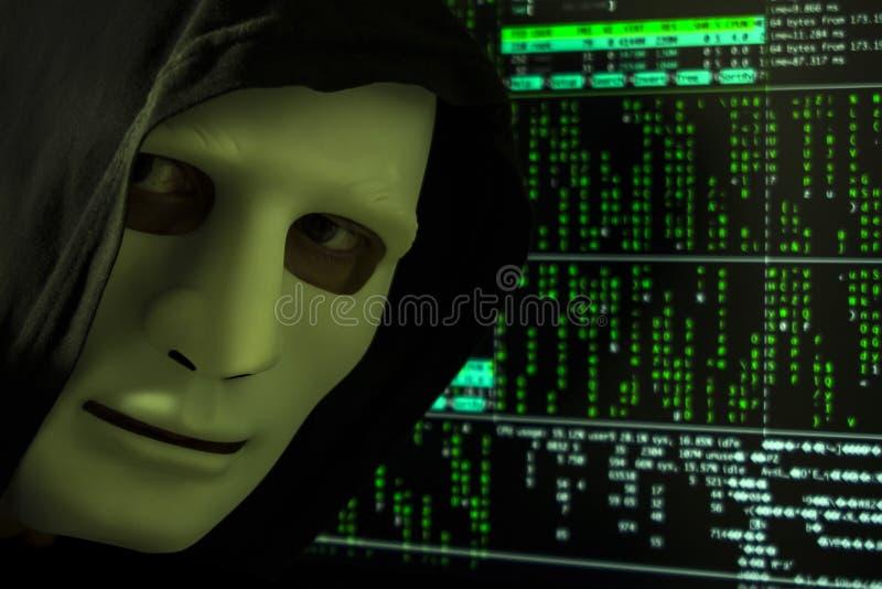 En hacker i huven och maskering på bakgrunden av den digitala koden royaltyfri foto