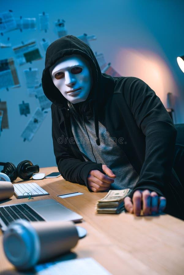 en hacker i maskering med bunten av pengar royaltyfri fotografi