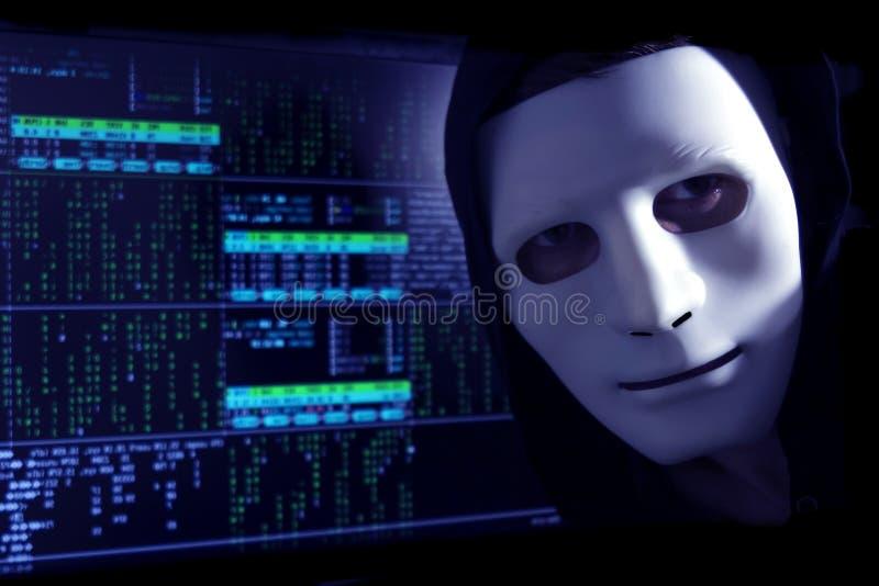 En en hacker i en maskering på en bakgrund av den binära koden ser in i ramen royaltyfria foton