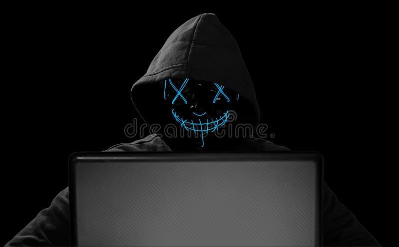 En hacker med den glödande maskeringen bak anteckningsbokbärbara datorn framme av det isolerade svarta begreppet för attack f royaltyfri illustrationer