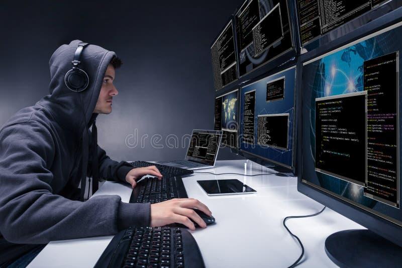 En hacker som använder åtskilliga datorer för att stjäla data royaltyfri foto