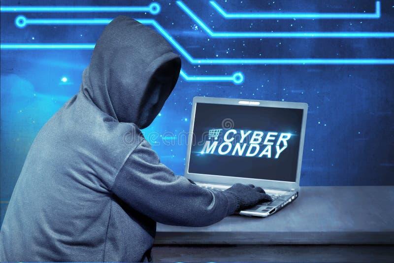 En hacker som använder bärbara datorn med textcyberen måndag på skärmen royaltyfria bilder