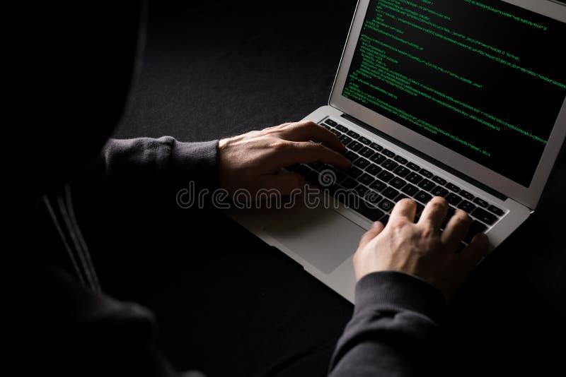En hacker som arbetar p? datorkod i m?rkret royaltyfri bild