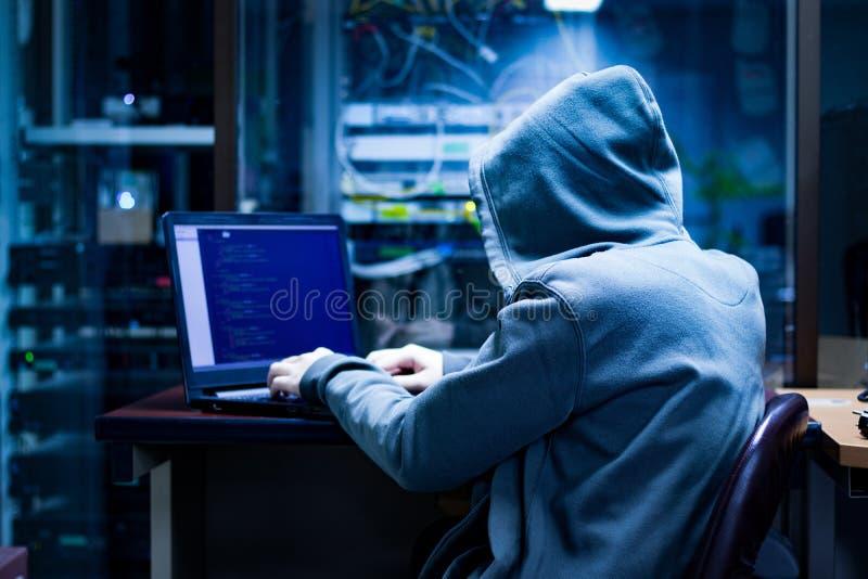 En hacker som försöker att dölja i mörkret fotografering för bildbyråer